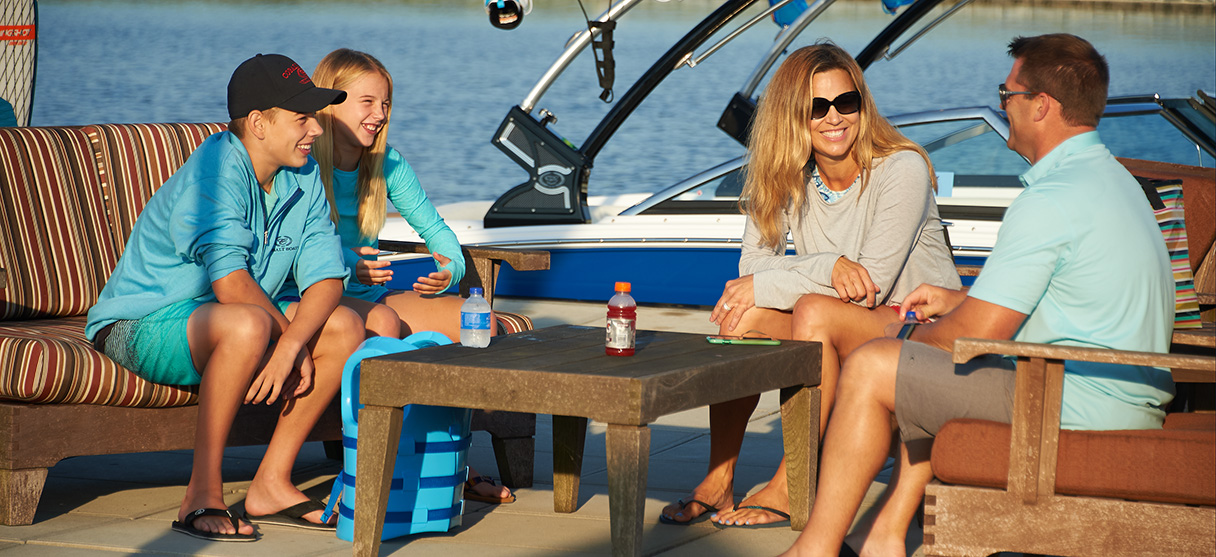 Family of Four Resting on Dock Outside of their Surf Series CS23 in Marine Blue