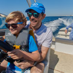 Father and Son Driving a Cobalt Boat with Mother and Daughter Relaxing in Rear of Boat