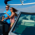 Couple Taking Cobalt Boat for a Drive with Wind in their Hair