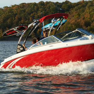 Cobalt Surf Series R3 in Knockout Red with Surfer Riding Wave Behind Boat