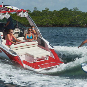 Cobalt Surf Series R5 in White and Knockout Red with Surfer Riding Wave Behind Boat